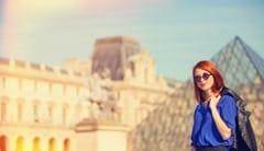 Redhead women near pyramid in Louver, Paris